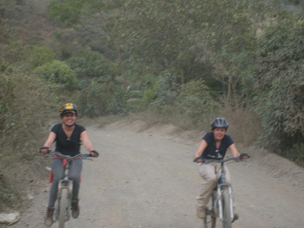 Machu Picchu Trilha Alternativa - Inka Jungle Trail - downhill. Duas pessoas montadas em bicicletas no fim do primeiro dia de trilha.
